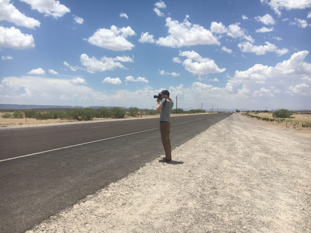 Thin man facing left with a camera held up to his face. He's standing beside a flat two-lane highway receding to the horizon with a blue sky full or puffy clouds.