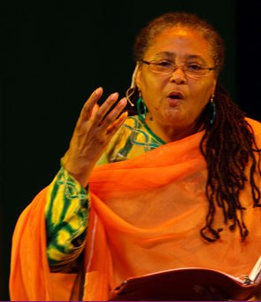 African America middle-aged woman with glasses and an orange wrap, performing.