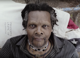 Video still of a black man with a lot of necklaces lying in a bed staring directly at the camera. From a Lonnie Holley video.