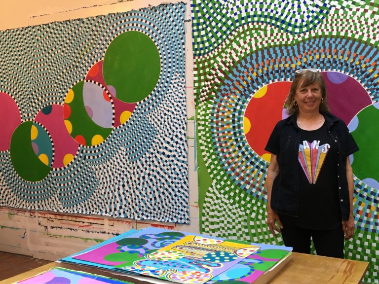 Artist Carol John stands in her studio in front of large geometric paintings
