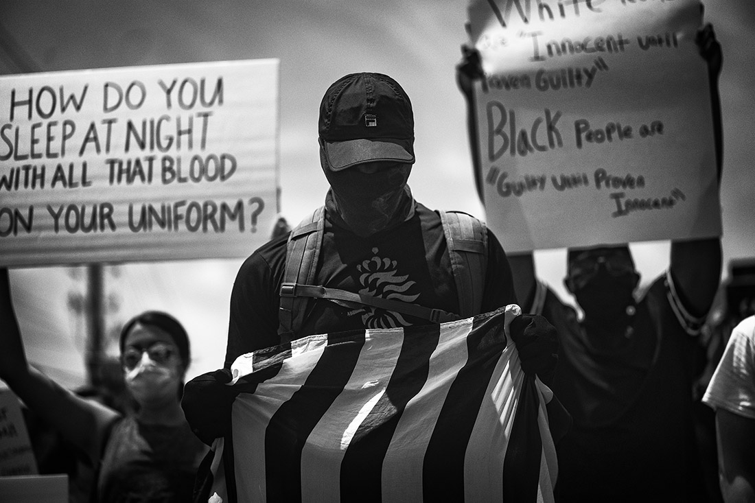 black and white photograph of a man holding an American flag, marching against police brutality