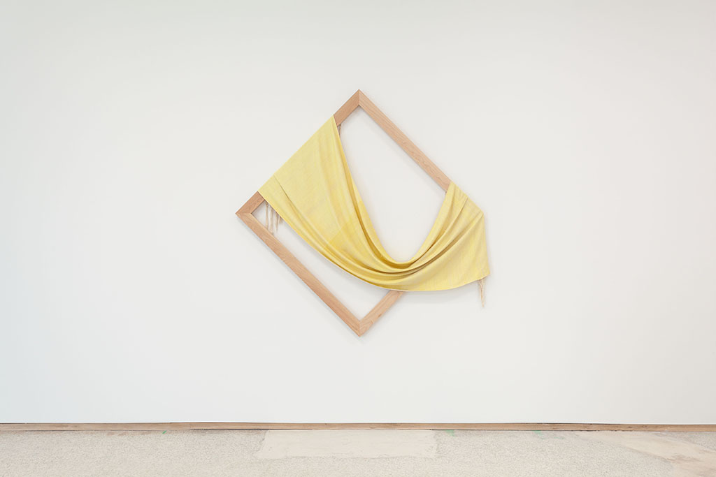 a diamond shaped frame draped with yellow cloth