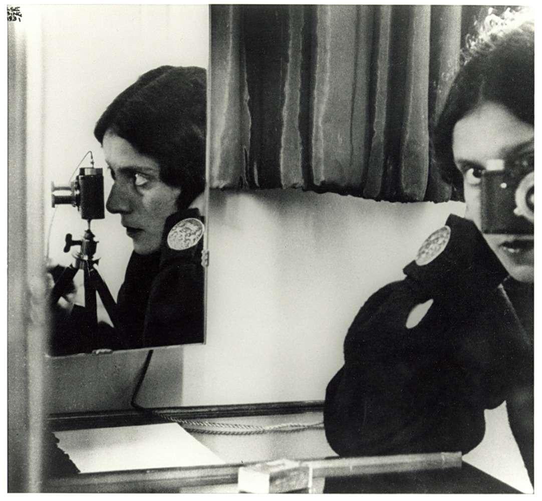 Self portrait of the photographer with several mirror reflecting different sides of her face behind the camera.