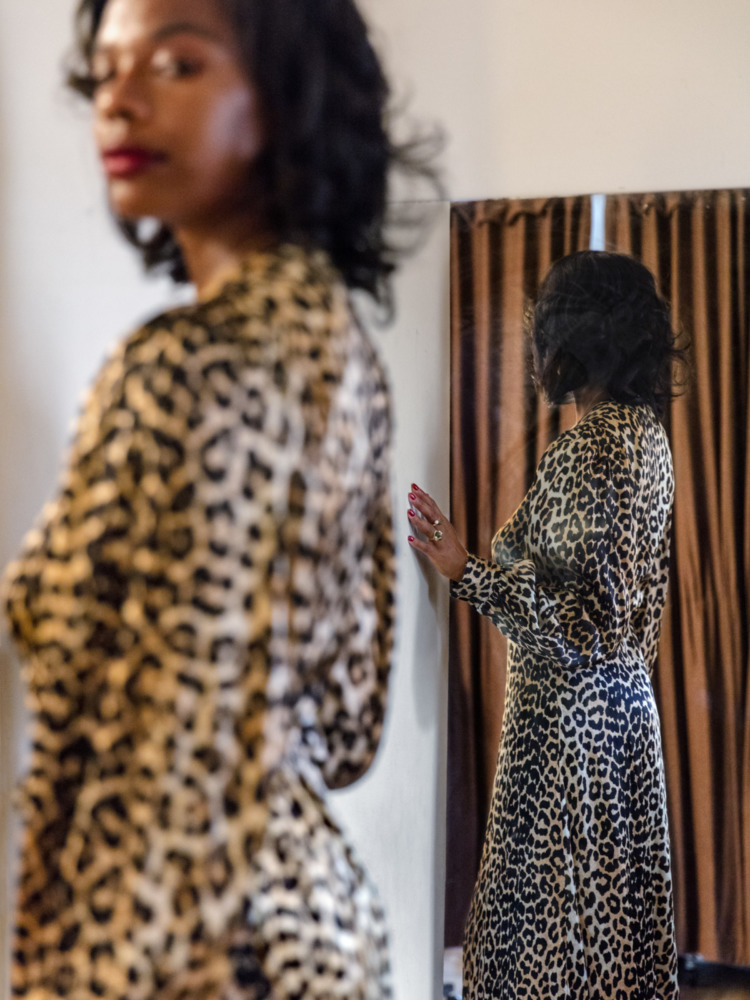 a black woman in a leopard print dress looks over her shoulder.