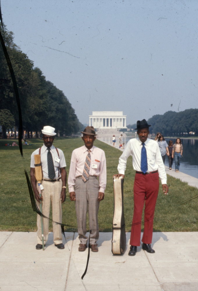 Three men stand in front of the Lincoln Memorial on the National Mall.