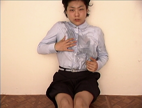 still from a film, an Asian woman with a distressed facial expression sits on the ground with their backing against a white wall, wearing a white button down and black pinstripe shorts, the chest of the shirt is wet with what looks like water